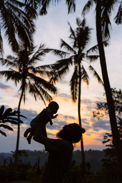 Father Holding Son Up Into the Air At Tropical Sunset