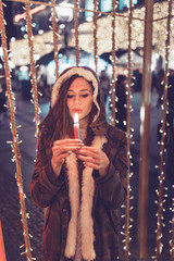 Beautiful young brunette woman enjoying Christmas or New Year night on a city street.