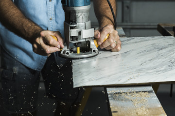 A man using a woodworking router to trim a laminate table top
