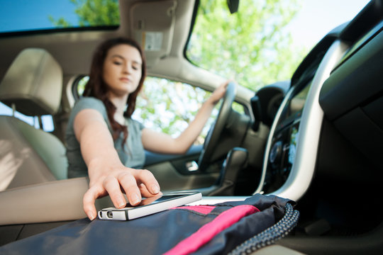 Driving: Teen Girl Reaching For Cell Phone While Driving