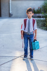 Back to school: Asian kid carrying a lunch bag in school