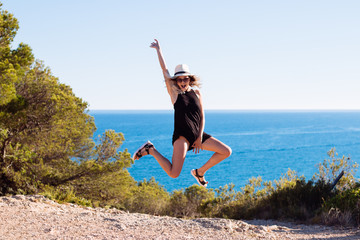 Portrait of young woman jumping on the field, with the sea background