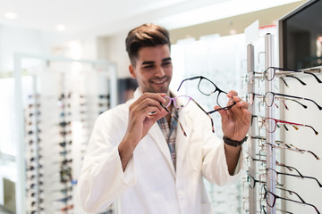 Handsome ophthalmologist choosing eyeglasses frame for his client in optical store.