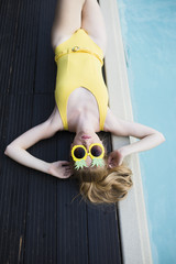 Young woman wearing yellow bikini sitting by the pool