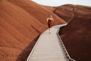 Young woman in red dress running through red painted hills.