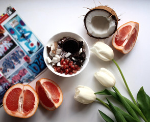 on the table a magazine, an hour with breakfast and sweets, fruits and flowers, coconut and grapefruit. summer relaxed morning with fresh colorful fruits