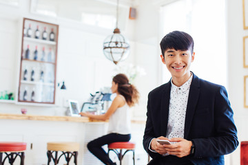 Portrait of a young businessman holding his phone working in a restaurant.