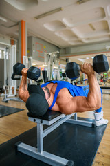 Bodybuilder working out chest muscles at the gym
