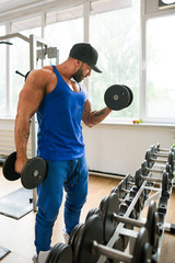 Muscular man working out biceps at the gym