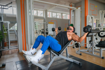 Bodybuilder working out chest muscles using dumbbells