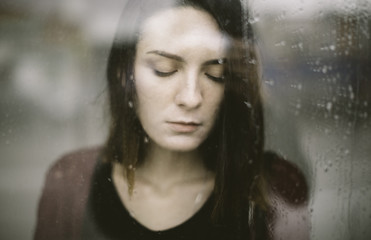 woman standing at the window and watching the rain