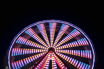 Spinning ferris wheel at night, abstract