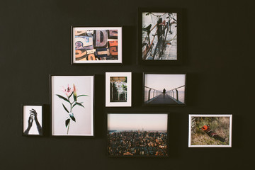 Variety of pictures hanging in a black wall.