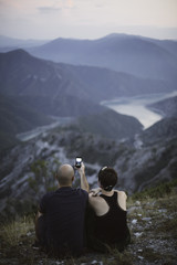 Couple enyoing at the mointain view and taking photos