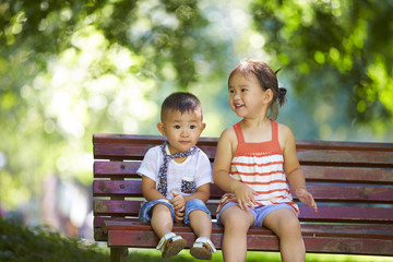 two happy little kids together outdoor sitting on the bench at park