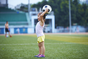 little asian or Chinese girl playing football outdoor in the football field