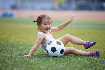 Little girl playing with football in the field