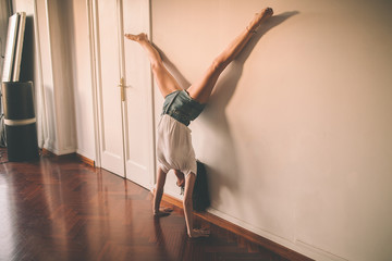 Young woman doing a headstand on a wall