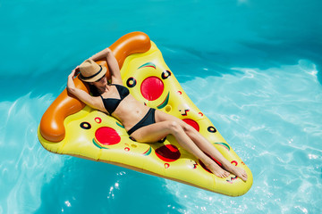 Woman on a pizza float in a swimming pool