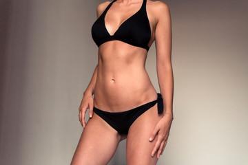 Fit female body in a black bikini