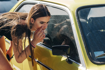 Young female model looking her self at rearview mirror of yellow oldtimer