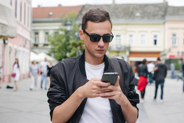 Portrait of a young male model with his phone on the street