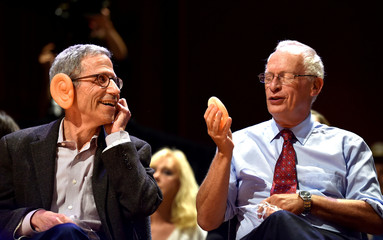Eric Maskin, 2007 Nobel laureate in Economics and Oliver Hart, 2016 Nobel laureate in Economics, try on plastic ears during the 27th First Annual Ig Nobel Prize Ceremony at Harvard University in Cambridge