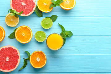Composition with glass of fresh juice and citrus fruits on color wooden background