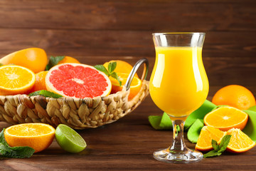 Composition with glass of fresh juice and citrus fruits in wicker basket on wooden table