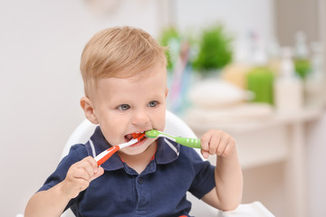 Adorable little boy brushing teeth at home