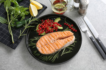 Grilled salmon steak with rosemary and red currant on plate