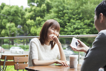 A couple talking casually on the cafe terrace while enjoying the smartphone