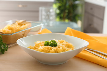 Plate with spaghetti squash on table