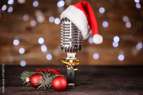 1834b32f43972 Christmas music concept. Microphone with hat and decoration on wooden table