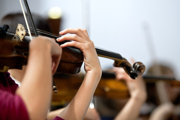 Hands of a girl playing the violin in the orchestra