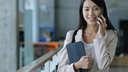 Business woman holding tablet and talk to cellphone
