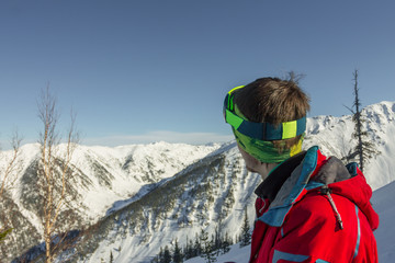 Portrait young man ski goggles looks to the mountains
