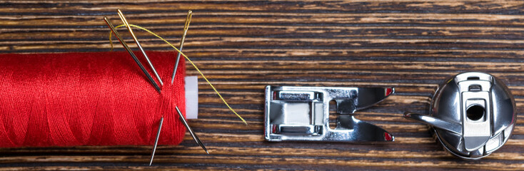 red coil thread on a wooden background, with a set of spare parts for a sewing machine