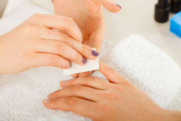 Woman making manicure using nail polish remover