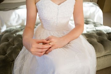 Midsection of bride trying wedding ring while sitting on bed