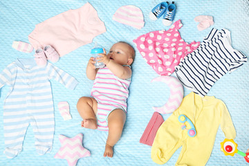 Little newborn baby different clothes on bed