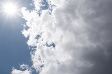sun and cumulus white clouds against a beautiful blue sky, bizar