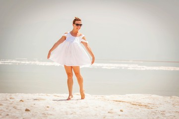 Young attractive Caucasian girl dancing barefoot on a salty island in the Dead Sea.