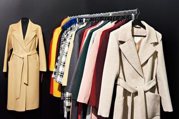 Women's coats on hanger in store on black