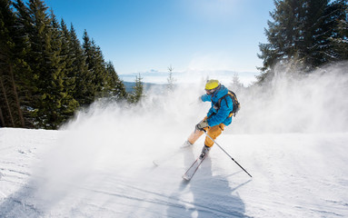 Skier skiing downhill in the mountains. Blue sky and winter forest on the background copyspace sports recreation winter ski resort people lifestyle active activity adrenaline equipment concept