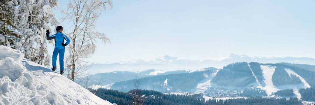 Panoramic shot of a female skier resting on top of the mountain observing nature at ski resort on a beautiful sunny winter day copyspace peaceful recreational vacation travel concept