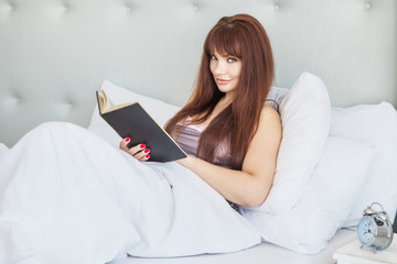 Beautiful caucasian girl is lying in bed with a black book. White bed and interior. Gray pajamas, nightgown. Smile. American.
