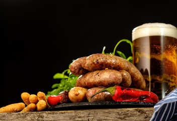 Grilled sausages with a glass of beer on a wooden table