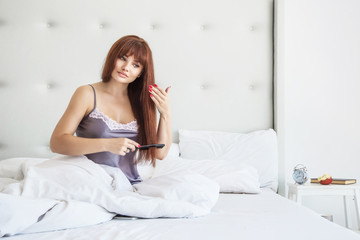 Beautiful Woman combing her long brown hair in a white bedroom sitting on the bed. Good morning. Hair care