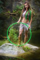 Frau mit Reifen steht am Wasser